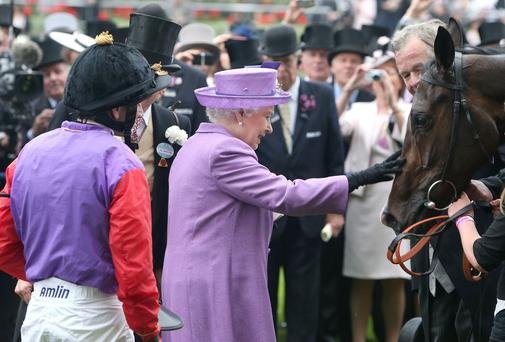 Queen Elizabeth II pats her horse Estimate after it won the Gold Cup ridden by jockey Ryan Moore (left) during Ladies' Day at Royal Ascot in 2014. Photo: PA