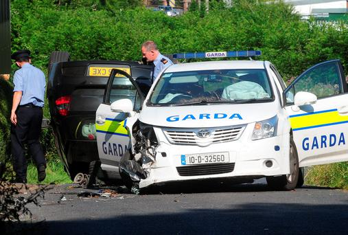 Gardai at the scene at Little Pallas, about two miles outside Portlaosie, Co Laois, where a car rammed a patrol car. Photograph: James Flynn/APX