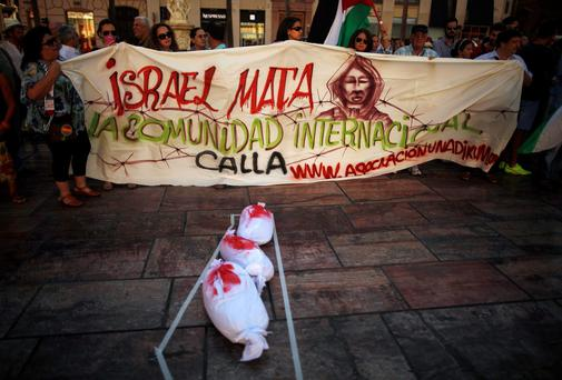 "People hold a banner next to sheets stained in red paint, mimicking blood, depicting the children, who medics said were killed by a shell fired by an Israeli naval gunboat, on a beach in Gaza City during a protest against Israel's military action in Gaza, at La Constitucion square in Malaga, southern Spain. Israel pounded targets across the Gaza Strip on Tuesday, saying no ceasefire was near as top U.S. and United Nations diplomats pursued talks on halting the fighting that has claimed more than 600 lives. The banner reads, ""Israel kills. The international community is silent"". Photo credit: REUTERS/Jon Nazca"