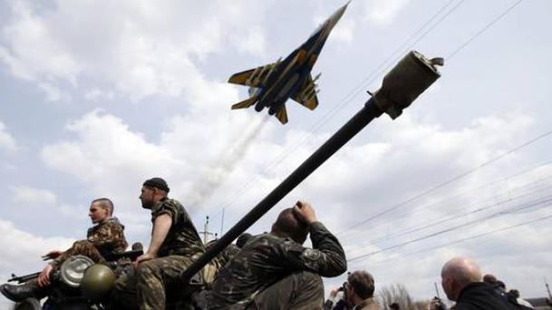 Fighter jet flies above as Ukrainian soldiers sit on an armoured personnel carrier in Kramatorsk, Ukraine (Photo: Reuters)