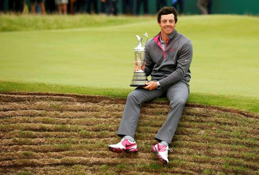 Rory McIlroy sits on the edge of a bunker as he holds the Claret Jug after winning the British Open Championship