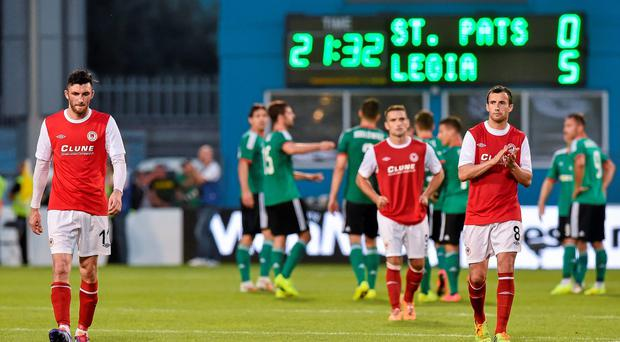 Dejected St Patrick's Athletic players Killian Brennan (left) and Keith Fahey trudge off the pitch after their Champions League second qualifying round defeat to Legia Warsaw at Tallaght Stadium. Photo: David Maher / SPORTSFILE