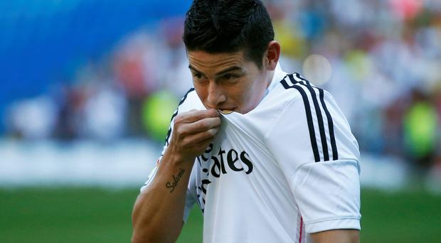 Colombia's soccer player James Rodriguez kisses his shirt during his presentation at the Santiago Bernabeu stadium in Madrid on Tuesday