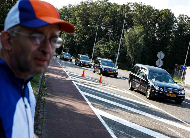 A man looks at the convoy of hearses with the remains of the victims of Malaysia Airlines MH17 downed over rebel-held territory in eastern Ukraine drives past on its way to a military base in Hilversum July 24, 2014