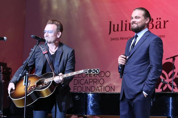 Bono and Leonardo Dicaprio speak onstage during the Leonardo Dicaprio Foundation Inaugurational Gala at Domaine Bertaud Belieu on July 23, 2014 in Saint-Tropez, France. (Photo by Pierre Suu/French Select/Getty Images)