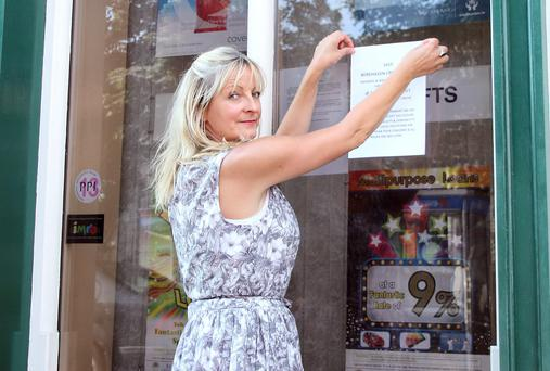 Protest organiser Georgina Goulding putting up posters at the offices of Berehaven Credit Union, Main Street, Castletownbere, West Cork. Photo: Niall Duffy