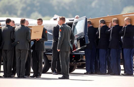 Coffins of the victims of Malaysia Airlines Flight MH17, downed over rebel-held territory in eastern Ukraine, are loaded into a hearse on the tarmac, during a national reception ceremony, at Eindhoven airport. Reuters