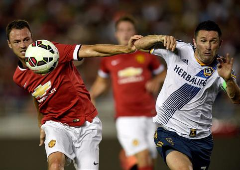 Manchester United defender Jonny Evans and Los Angeles Galaxy forward Robbie Keane battle for the ball
