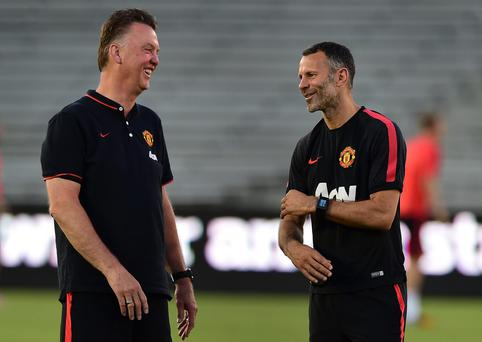 Manchester United assistant coach Ryan Giggs chats with new head coach Louis van Gaal