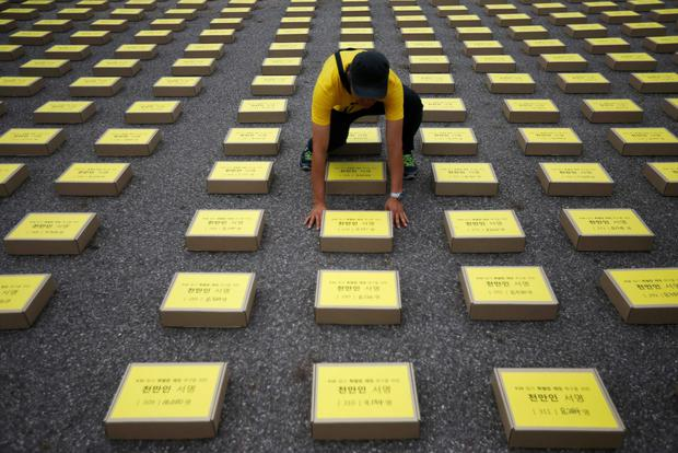 A man arranges a box containing signatures of South Koreans petitioning for the enactment of a special law after the mid-April Sewol ferry disaster, at Yeouido Park in Seoul July 15, 2014. The words on the box read,