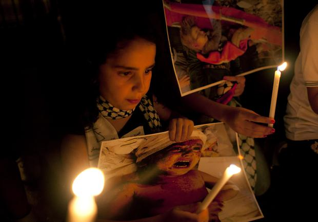 A girl holds a candle and a poster with a picture of an injured Palestinian child during a protest in the West Bank city of Ramallah