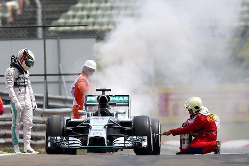 Lewis Hamilton of Great Britain and Mercedes GP looks on as fire marshalls extinguish the fire in his car during qualifying ahead of the Hungarian Formula One Grand Prix at Hungaroring