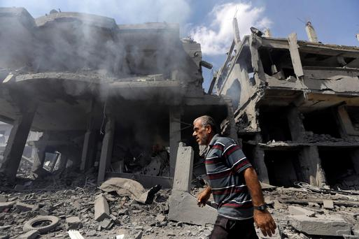 A Palestinian man walks by buildings heavily damaged by Israeli strikes in Beit Hanoun, northern Gaza Strip