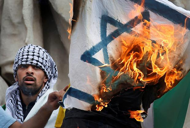 Pro Palestinian protester burns an Israeli flag during demonstration banned by police, in support of Gaza in central Paris