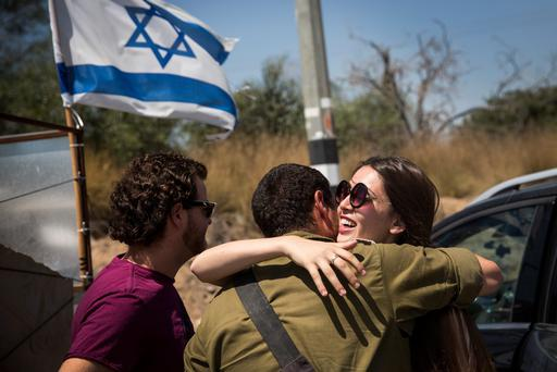 ZIKIM, ISRAEL - JULY 26: A soldier meets with his loved ones during a 12-hour ceasefire just outside the militarized zone near the Israeli-Gaza border on July 26, 2014 near Zikim, Israel. After nearly three weeks of the Israeli operation
