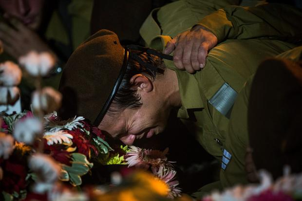 An Israeli soldier weeps over the casket of Private First Class Jordan Bensimon during his funeral