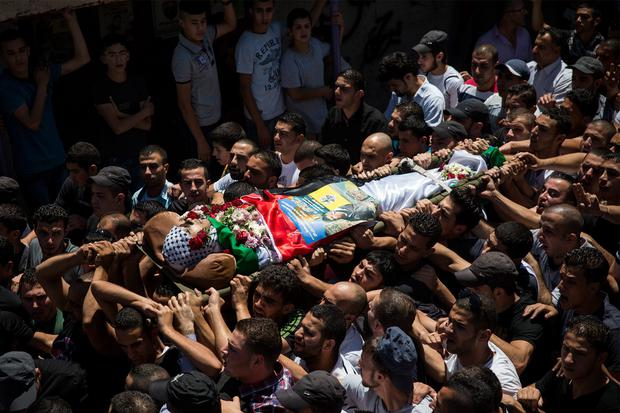 The body of Mohammed al-Araj is carried through the streets to the cemetary during his funeral