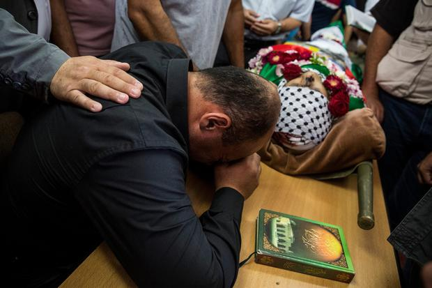 Men mourn over the body of Mohammed al-Araj at his funeral