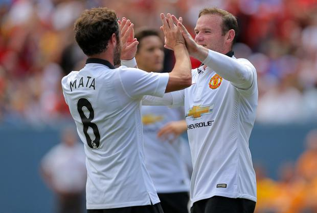 Manchester United's Wayne Rooney celebrates his second goal with teammate Juan Mata during the first half of the game against Roma in Denver. Photo: Justin Edmonds/Getty Images