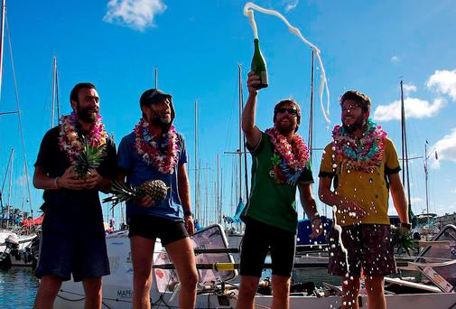 Philip Cavanagh cracks open the champagne with his fellow crew members after arriving in Hawaii