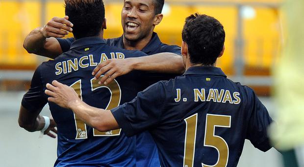 Scott Sinclair (12) celebrates with Gael Clichy (C) and Jesus Navas (15) after a goal against AC Milan during a friendly