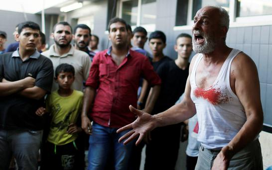 The father of a Palestinian boy reacts following his death at a hospital in Gaza City