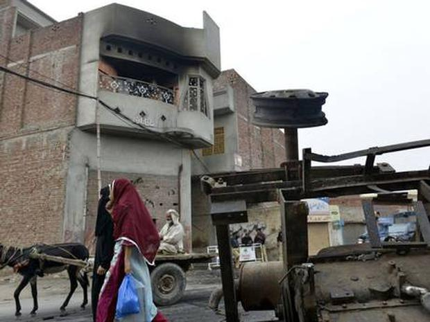 Pedestrians walks past the smoke-charred house of an Ahmadi resident following an attack by an angry mob in the low-income Arafat Colony