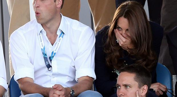 Britain's Kate Duchess of Cambridge, right, and Prince William, left, react as they watch the women's field hockey match between Wales and Scotland