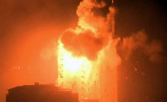 In this image taken from video an explosion hits the media complex that houses the offices of Hamas-run Al Aqsa television and radio in central Gaza City early on Tuesday, July 29, 2014.