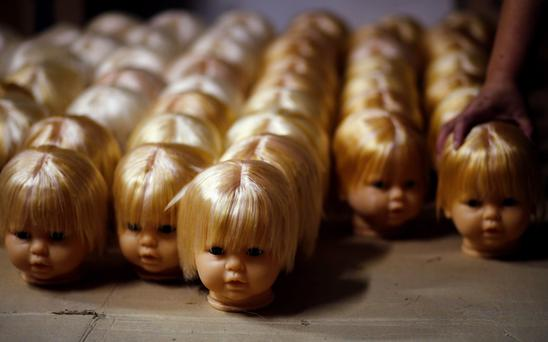 An employee arranges doll heads inside the toy factory owned by Norberto Garcia in Buenos Aires