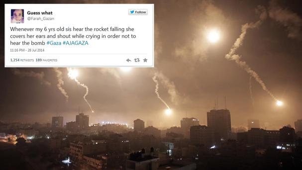 Gaza teenager live tweets as Israeli forces' flares light up the night sky of Gaza City (AP Photo/Khalil Hamra)