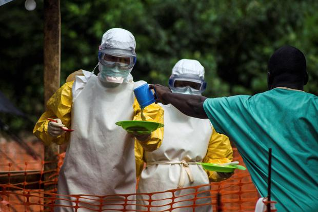 Medical staff working with Medecins sans Frontieres (MSF) prepare to bring food to patients kept in an isolation area at the MSF Ebola treatment centre in Kailahun. Reuters