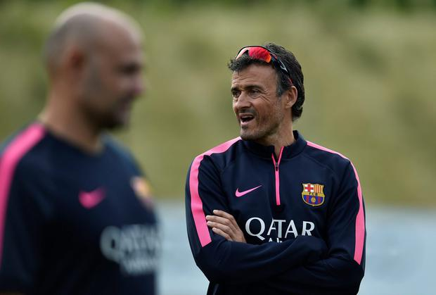 Barcelona coach Luis Enrique runs his eye over his squad during a session as part of their pre-season training week at St George's Park in England. Photo: REUTERS/Toby Melville