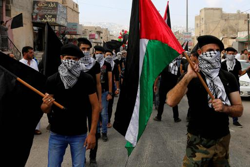 Palestinian refugees, carrying black and Palestinian flags, attend a demonstration calling for an end to the Israeli offensive in the Gaza Strip, after Eid al-Fitr prayers at Al-Baqaa Palestinian refugee camp, near Amman. Reuters