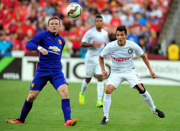 Wayne Rooney fights for a loose ball with Inter Milan's Ruben Botta