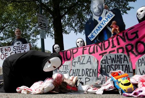 Codepink activists, dressed to symbolize those wounded and killed in Gaza, rally outside the Israeli Embassy in Washington. REUTERS/Yuri Gripas