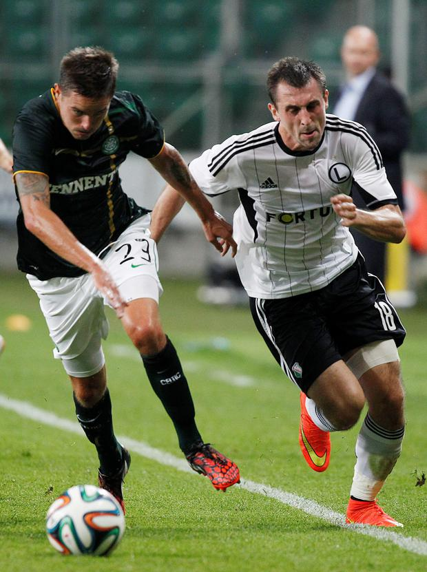 Celtic's Mikael Lustig, left, and Legia's Michal Kucharczyk challenge for the ball during the Champions League first leg third qualifying round soccer match between Legia Warsaw and Celtic Glasgow in Pepsi Arena in Warsaw, Poland, Wednesday July 30, 2014. (AP Photo/Czarek Sokolowski)
