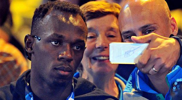 Self distraction: Usain Bolt poses for pictures with a fan as he watches the Jamaican netball team Photo: GETTY IMAGES