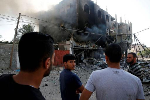 Palestinians gather near a burning building that police said was destroyed by an Israeli Air strike in Gaza City. Reuters