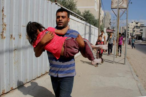 A Palestinian carries his daughter as they flee, following an Israeli airstrike on an apartment building in Rafah. AP
