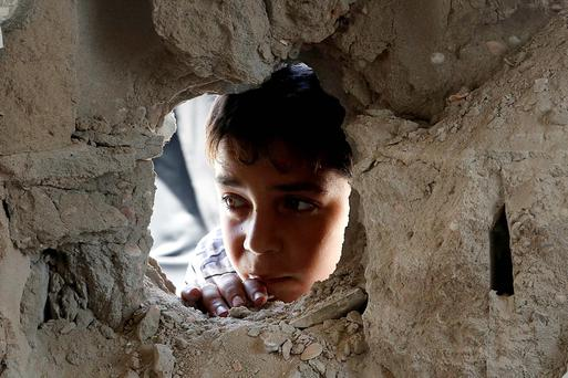 A boy looks through a hole on the wall made by the shelling at the Abu Hussein UN school in the Jebaliya refugee camp in the northern Gaza Strip. AP