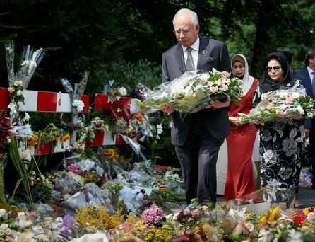 Malaysian Prime Minister Najib Razak, front, and his wife Datin Sri Rosmah Mansor, right, lay flowers among other flower tributes outside a military barracks where forensic experts are working to identify bodies and human remains recovered from the wreckage of Flight 17, in the central city of Hilversum, Netherlands. AP