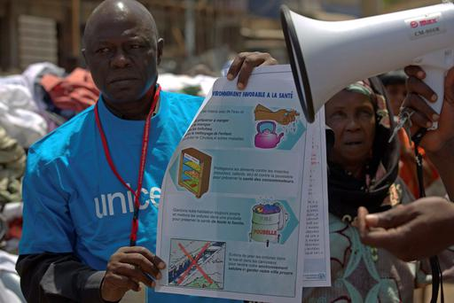 A UNICEF worker holds a poster bearing information about best practices to prevent the spread of the Ebola virus, in Conakry, Guinea. Reuters / UNICEF