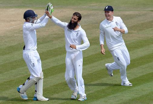 England's Moeen Ali (c) celebrates with teammates after taking the wicket of India's Mohammed Shami claiming his fifth wicket during day five of the Third Investec Test match