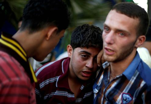 Relatives of Palestinians, whom medics said were killed in an Israeli air strike on their van, grieve at a hospital Gaza City July 31, 2014.