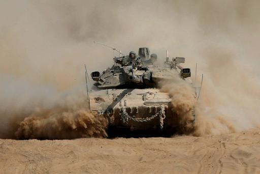 An Israeli tank manoeuvres outside the northern Gaza Strip after crossing into Israel from Gaza July 31, 2014. Israeli Prime Minister Benjamin Netanyahu, facing international alarm over a rising civilian death toll in Gaza, said on Thursday he would not accept any ceasefire that stopped Israel completing the destruction of militants' infiltration tunnels. Gaza officials say at least 1,372 Palestinians, most of them civilians, have been killed in the battered territory and nearly 7,000 wounded. Fifty-six Israeli soldiers have been killed in Gaza clashes and more than 400 wounded. Three civilians have been killed by Palestinian shelling in Israel. REUTERS/Baz Ratner (ISRAEL - Tags: CIVIL UNREST MILITARY POLITICS TPX IMAGES OF THE DAY CONFLICT)