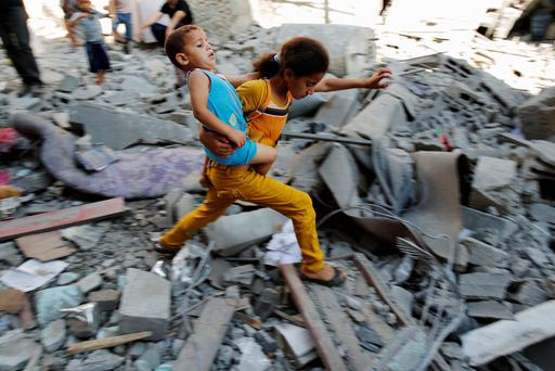 A Palestinian girl carries a child across rubble from a building that police said was destroyed by an Israeli air strike, in the Burij refugee camp in the central Gaza Strip. Reuters
