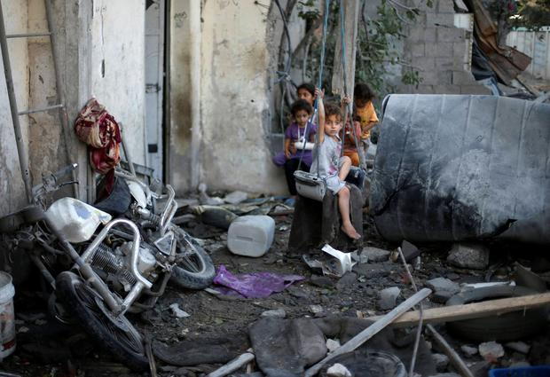 A Palestinian girl sits on a swing outside her family's house, which witnesses said was damaged in an Israeli air strike