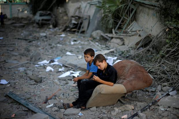 Palestinian boys sit on a sofa outside their house