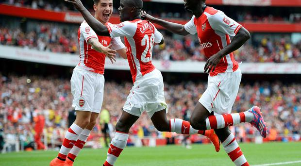 Arsenal's Yaya Sanogo (R) and Hector Bellerin (L) celebrate after Joel Campbell (C) scored against Benfica